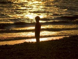 Young boy watching the sunset. by mohamadfazli